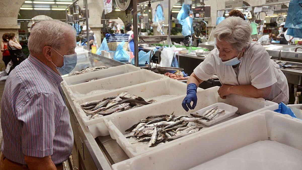 Un cliente de la plaza de abastos se dispone a comprar sardinas en uno de los puestos.