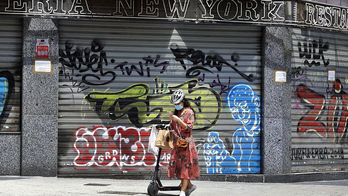 Una mujer consulta su teléfono frente a un local cerrado de València, en mayo. | M. Á. MONTESINOS