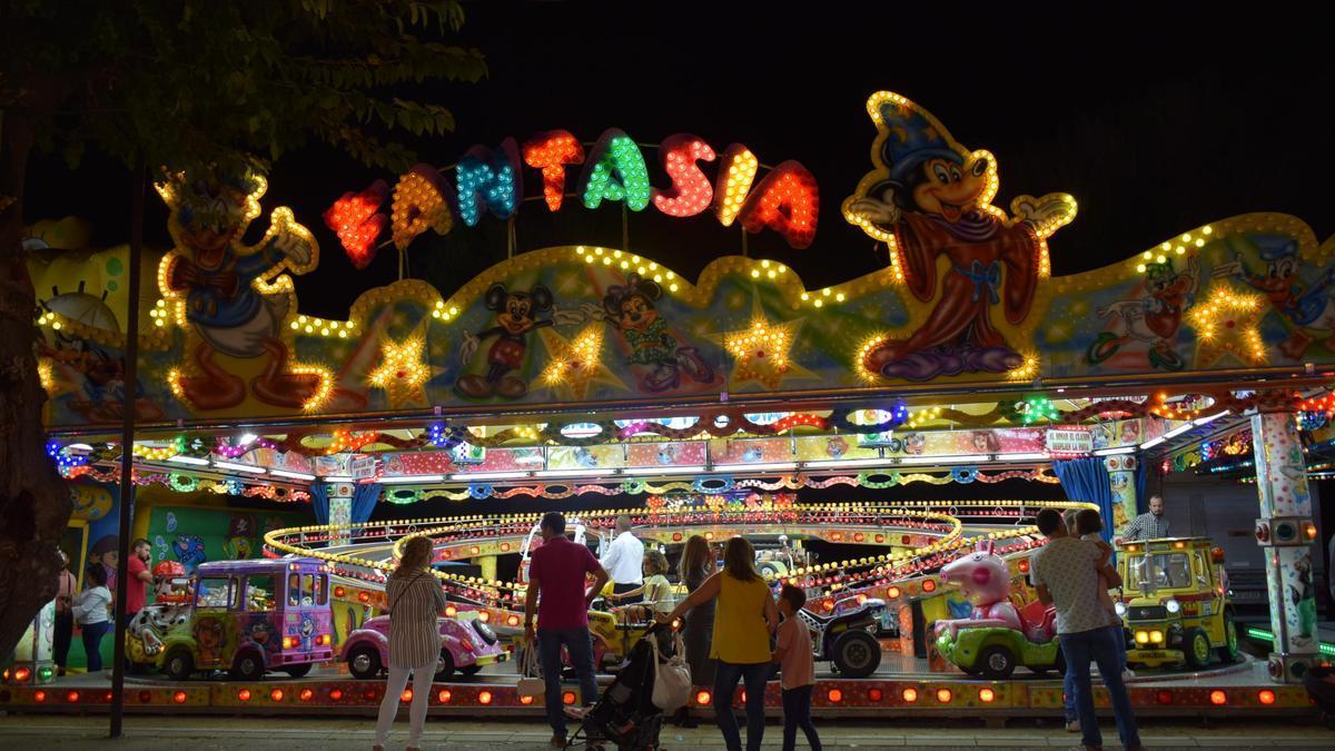Varias personas miran una atracción infantil en Almodóvar del Río.