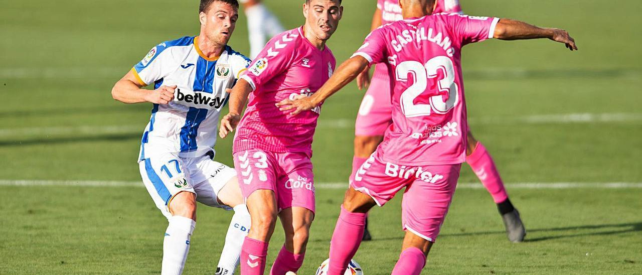 Sergio Ruiz (3) es acosado por un jugador rival mientras Dani Castellano despeja el balón, en el choque ante el Leganés.