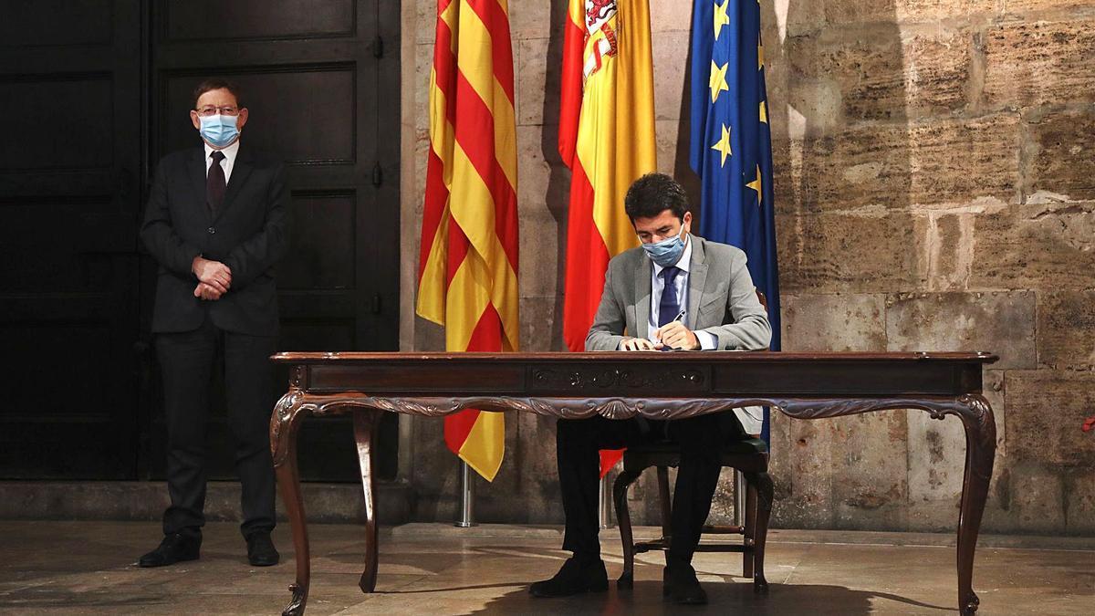 Carlos Mazón firmando el convenio para sumarse al nuevo fondo de Transparencia ante la presencia de Ximo Puig.   INFORMACIÓN