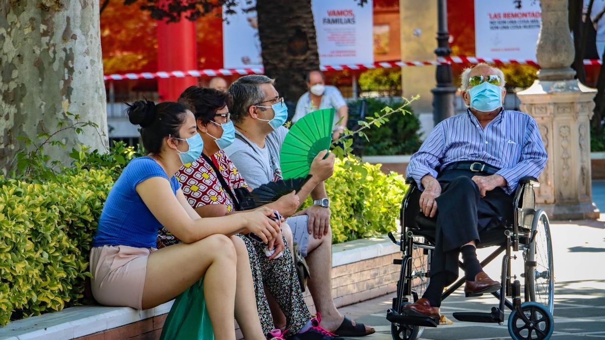 Personas sentadas en la plaza de San Francisco de Badajoz durante una jornada calurosa.
