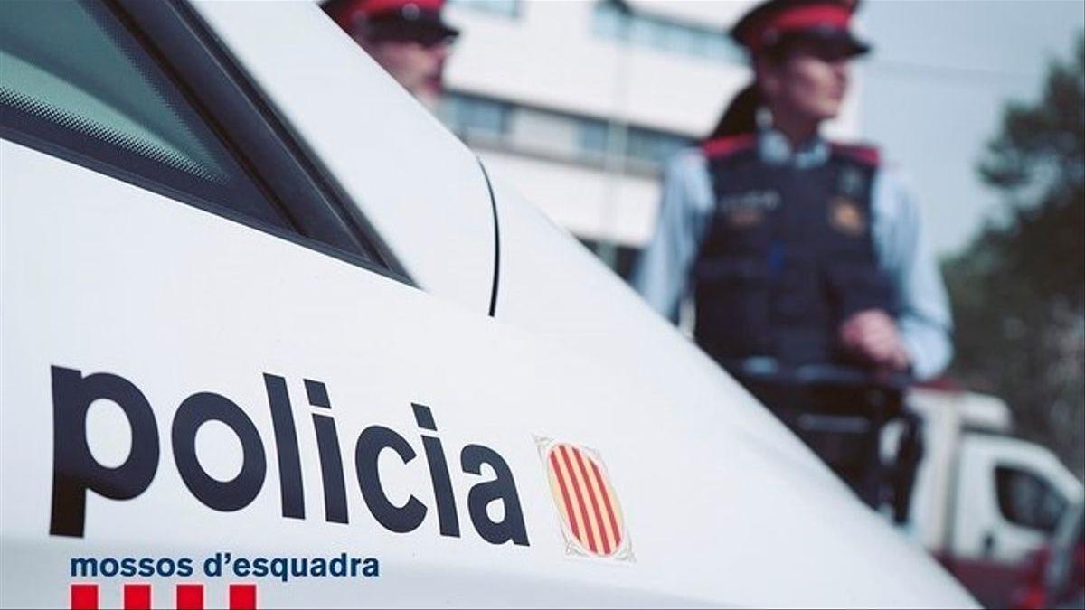Una pareja de Mossos d'Esquadra, junto a un vehículo del cuerpo policial.