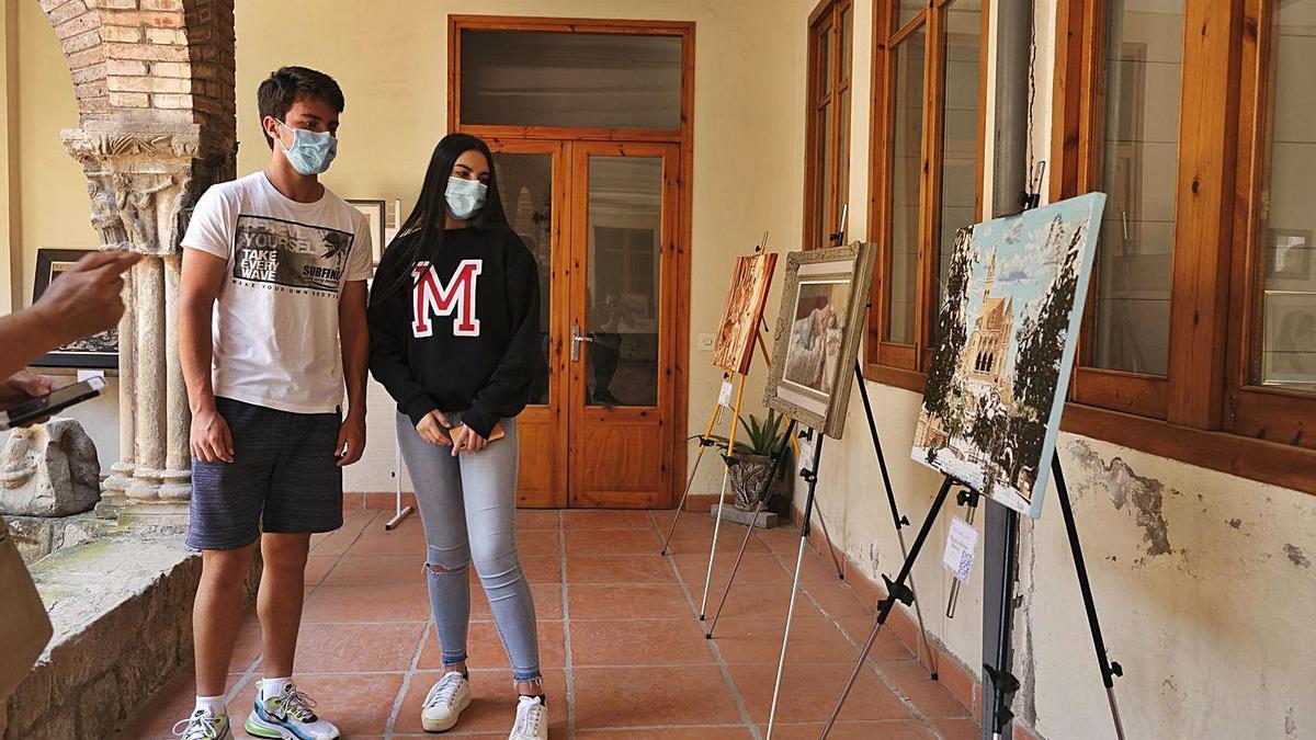 Marcel Morales i Marina Segovia miren el quadre de l'avi de la jove estudiant de Cal Gravat   ALEX GUERRERO