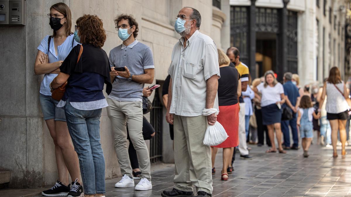 Personas esperan a las puertas del Banco de España de Barcelona