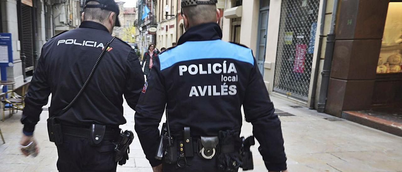 Un agente de la Policía Nacional y otro de la Local recorren la calle de La Fruta, en Avilés.   Ricardo Solís