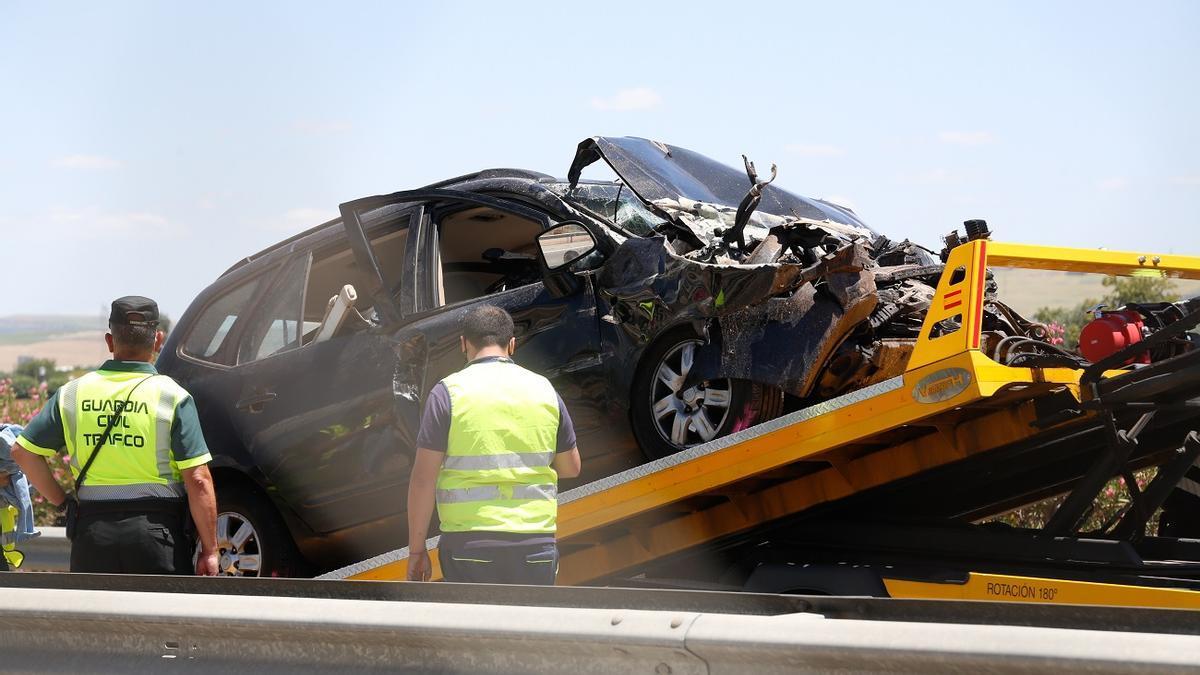Una grúa retira el vehículo accidentado del lugar del siniestro, en la A-4.
