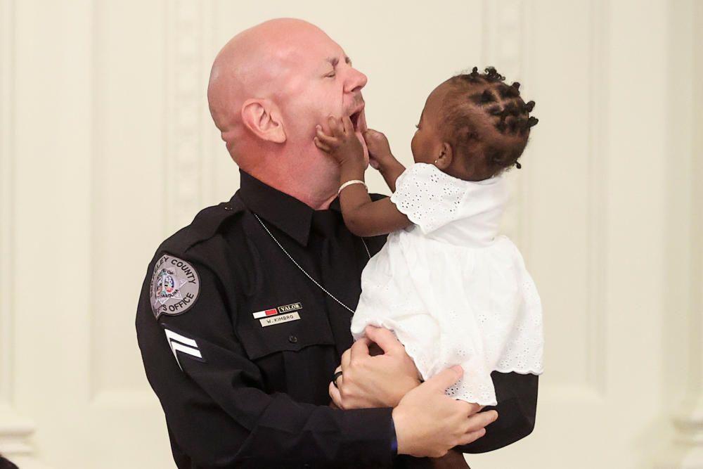 La bebé de un año Ryleigh Boyd agarra la cara del alguacil William Kimbro durante un debate organizado por el presidente Donald Trump en la Casa Blanca. Foto: Reuters