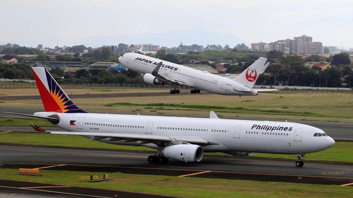 Un avión Boeing 767-300ER despega mientras un avión Airbus A330-300 permanece en pista.