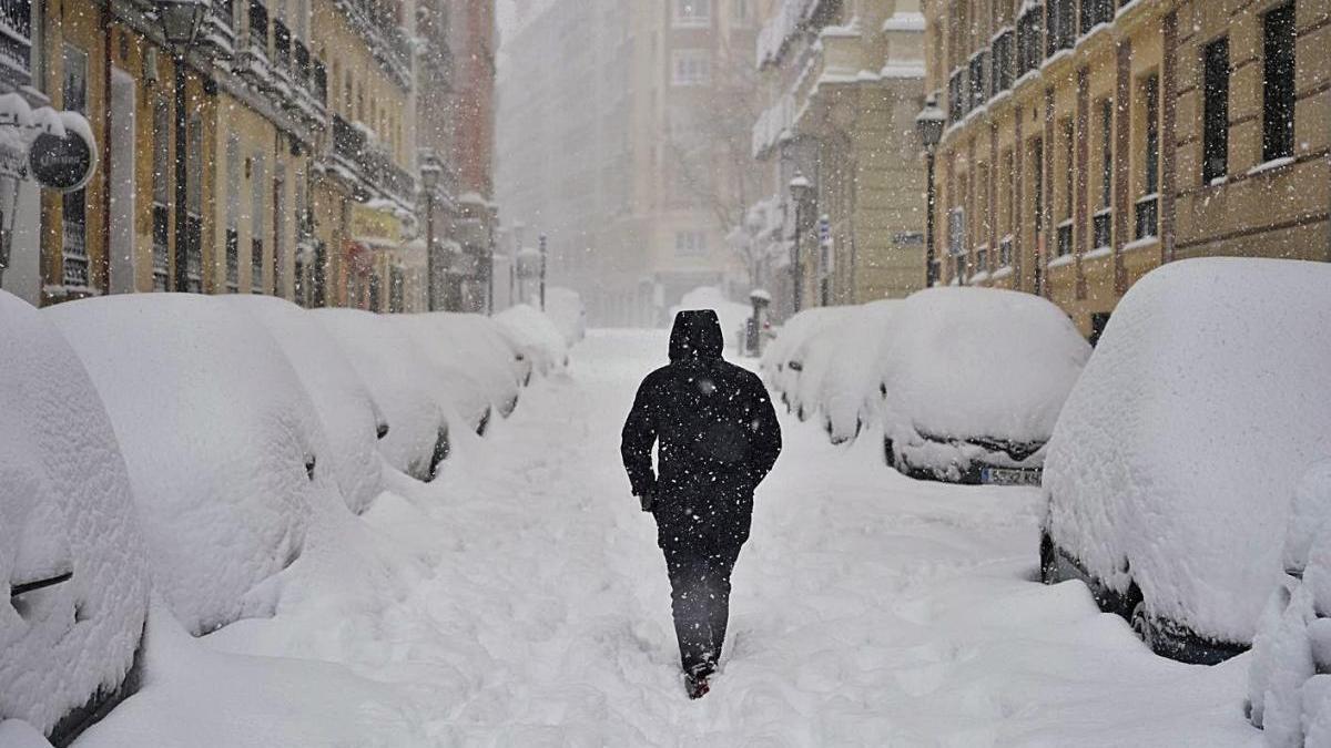 Un ciutadà al costat de cotxes nevats, a Madrid