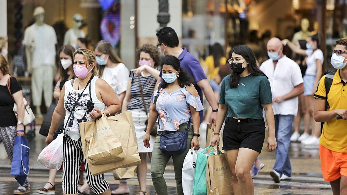 Varias personas pasean por València en el último domingo con mascarilla obligatoria.  | EDUARDO RIPOLL