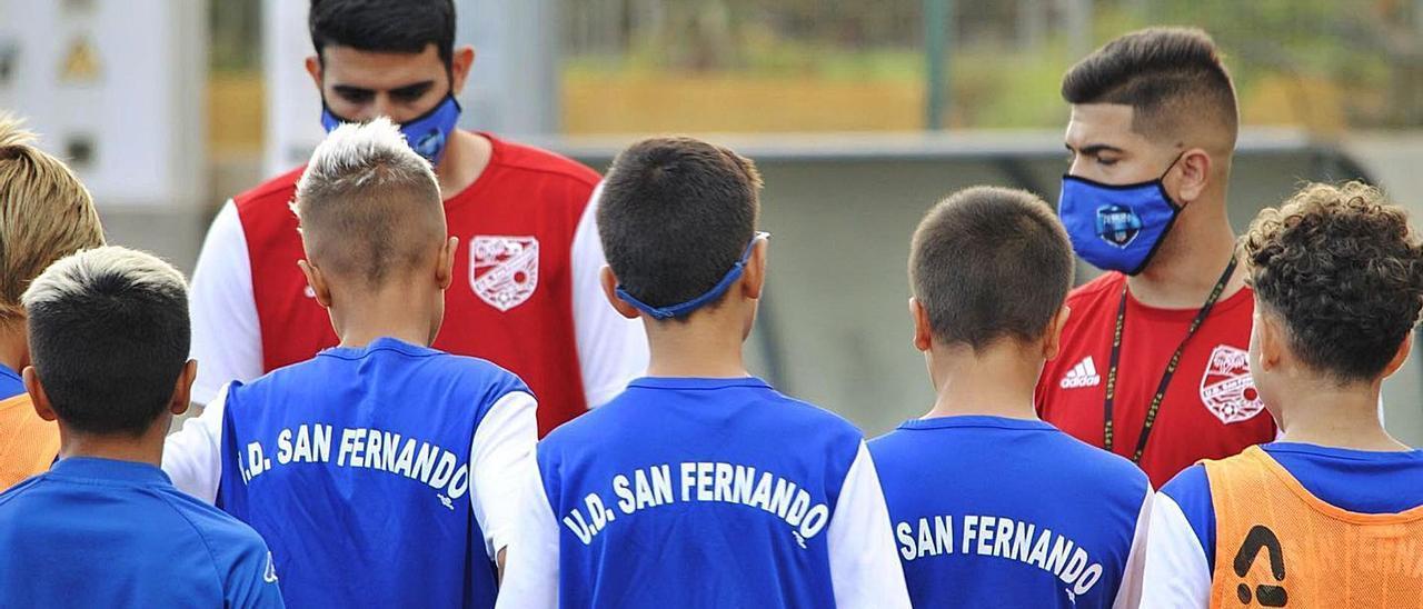 Uno de los equipos de la base de la UD San Fernando reciben instrucciones de sus entrenadores.    