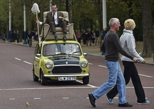 British comedian Atkinson, in character as 'Mr Bean', rides on a Mini car, during a publicity event along The Mall in central London