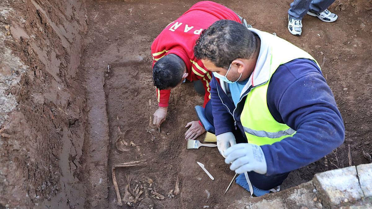 Dos operarios examinan los restos óseos de una persona en el cementerio de San Rafael de Córdoba.
