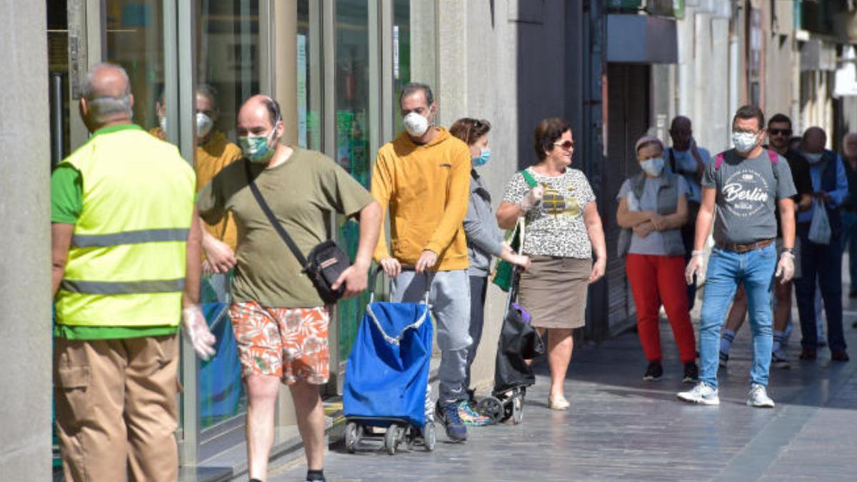 Un grupo de ciudadanos hace cola a las puertas de un supermercado de la capital grancanaria.