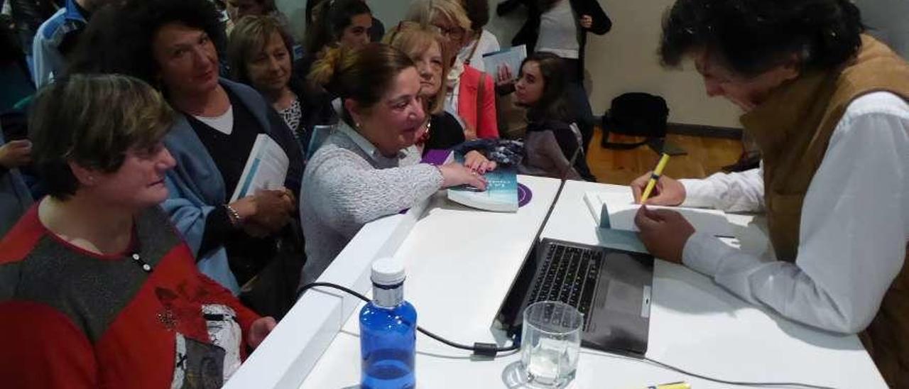 Carlos López Otín firmando libros en la Casa de Cultura Severo Ochoa de Noreña.