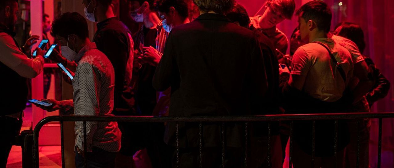 Revisión de pasaporte covid en la entrada de una discoteca.