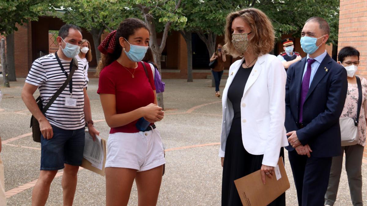 La consellera d'Empresa i Coneixement, Maria Àngels Chacón, parlant amb una estudiant que s'examinava de les Proves d'Accés a la Universitat en el pati de l'institut del Cap Norfeu de Roses