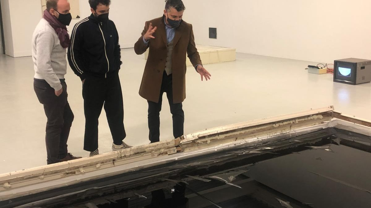 Comisario y artista muestran una de las piezas de la exposición al director del ICA.