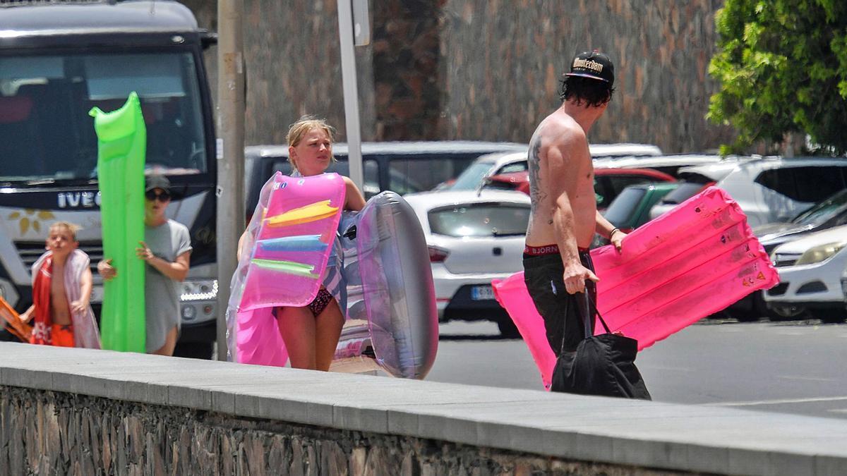 Bañistas ayer se dirigen con colchonetas a Playa del Inglés.     JUAN CARLOS CASTRO
