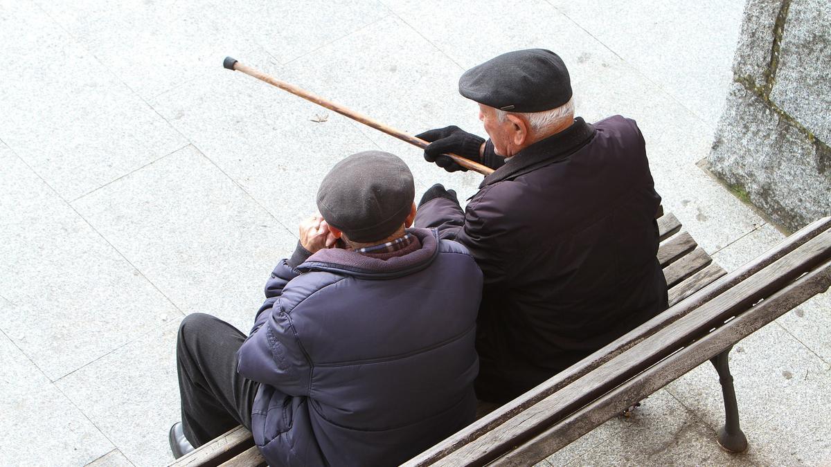 Dos ancianos conversan sentados en un banco.