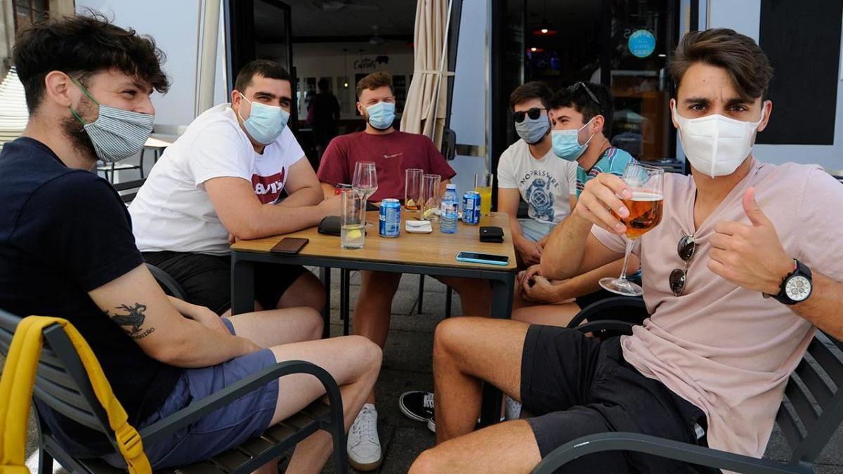 Jóvenes con mascarilla en una cafetería