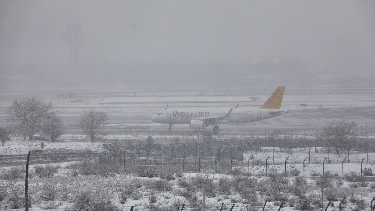 Un avión se intuye entre la densa niebla del aeropuerto de Madrid-Barajas