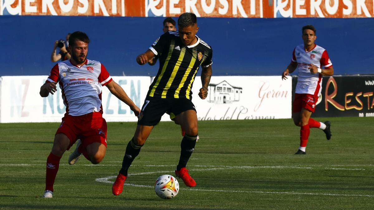 Juanjo Narváez pugna por un balón con un futbolista del Calahorra durante el amistoso en La Planilla.