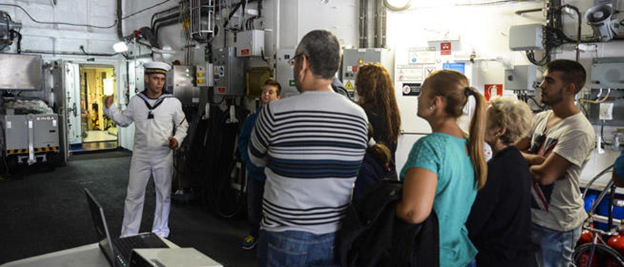 Un grupo de visitantes atentos a las explicaciones de un marino, en el interior del buque.