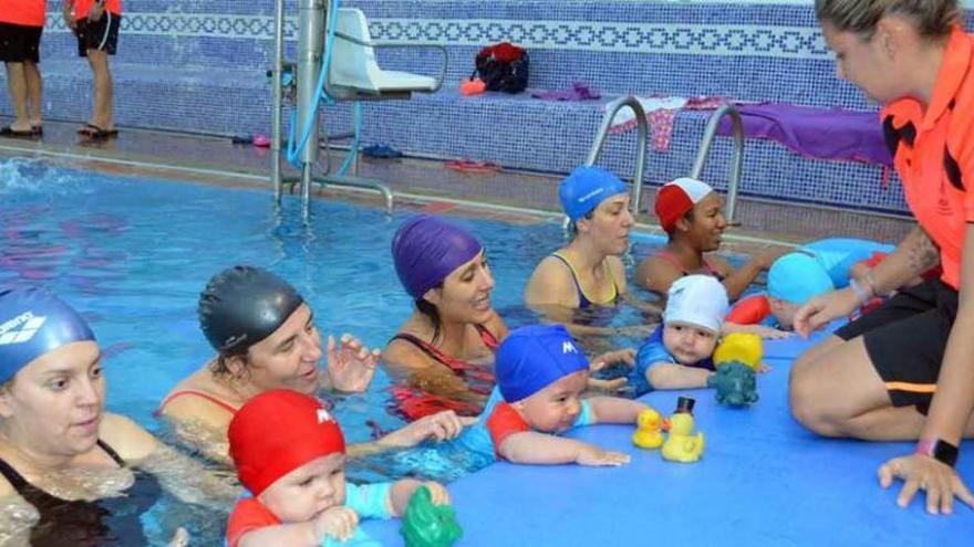 La monitora atrae a los bebés con juguetes y los pequeños se sostienen en la orilla sin ayuda de las mamás.