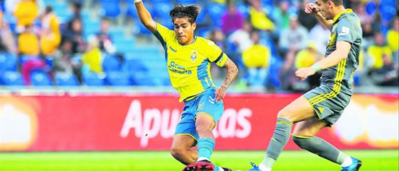 Fede Varela, centrocampista de la UD Las Palmas, cubre el balón ante la oposición de Iván Alejo, extremo del Cádiz.