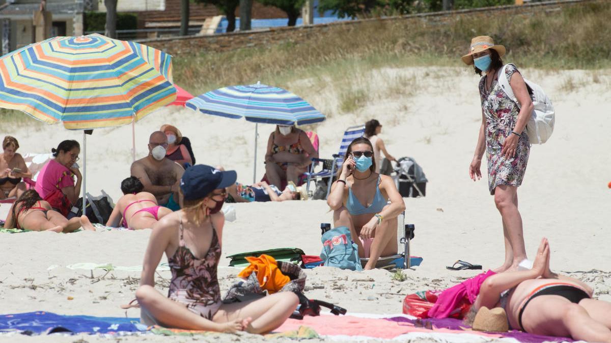 Varias personas toman el sol con mascarilla en la playa A Rapadoira, en Foz / Carlos Castro