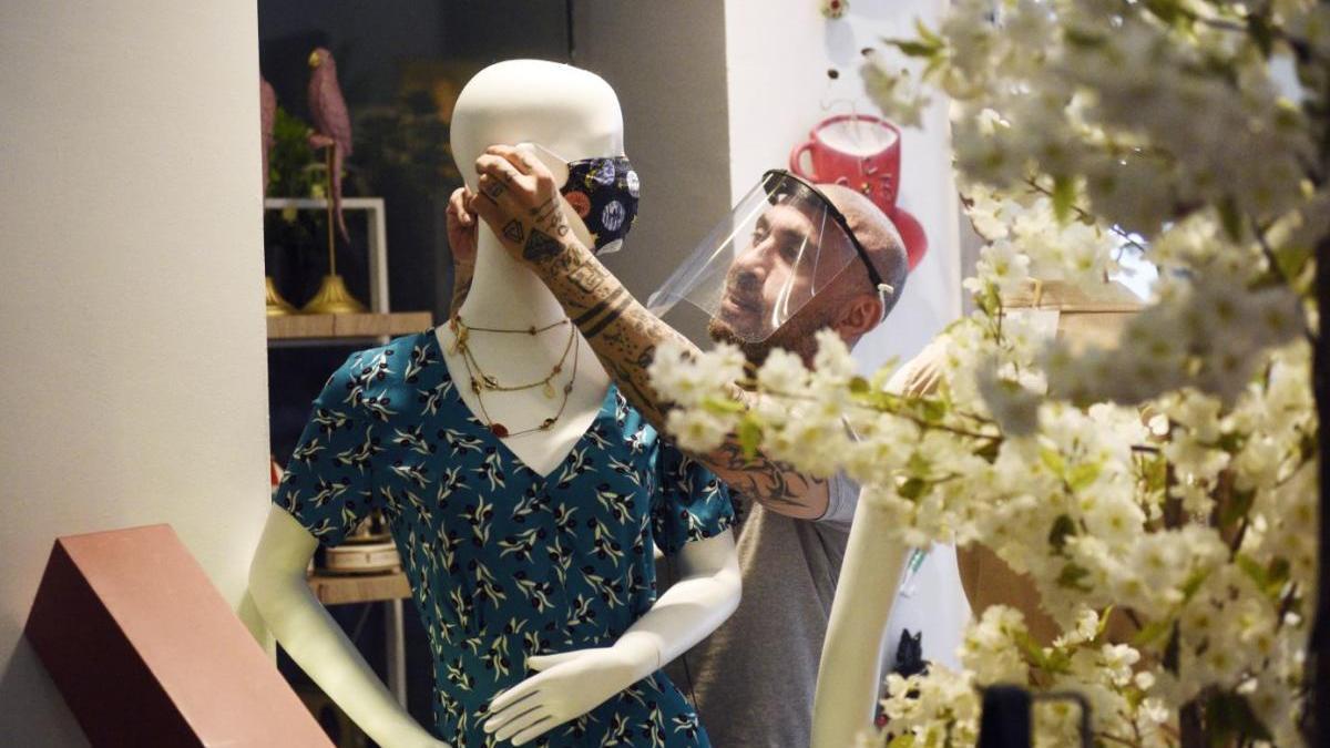 Una persona coloca una mascarilla a un maniquí en Murcia.