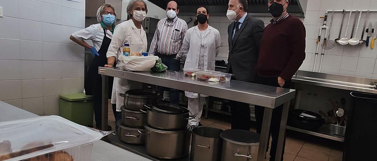 Por la derecha, Carlos Muñiz, presidente de Amicos; José Luis Llamazares (vicepresidente); Natalia López; José Manuel Iglesias (tesorero); y  Montserrat Galán y Araceli Rodríguez (voluntarias), en la cocina.   A. Velasco