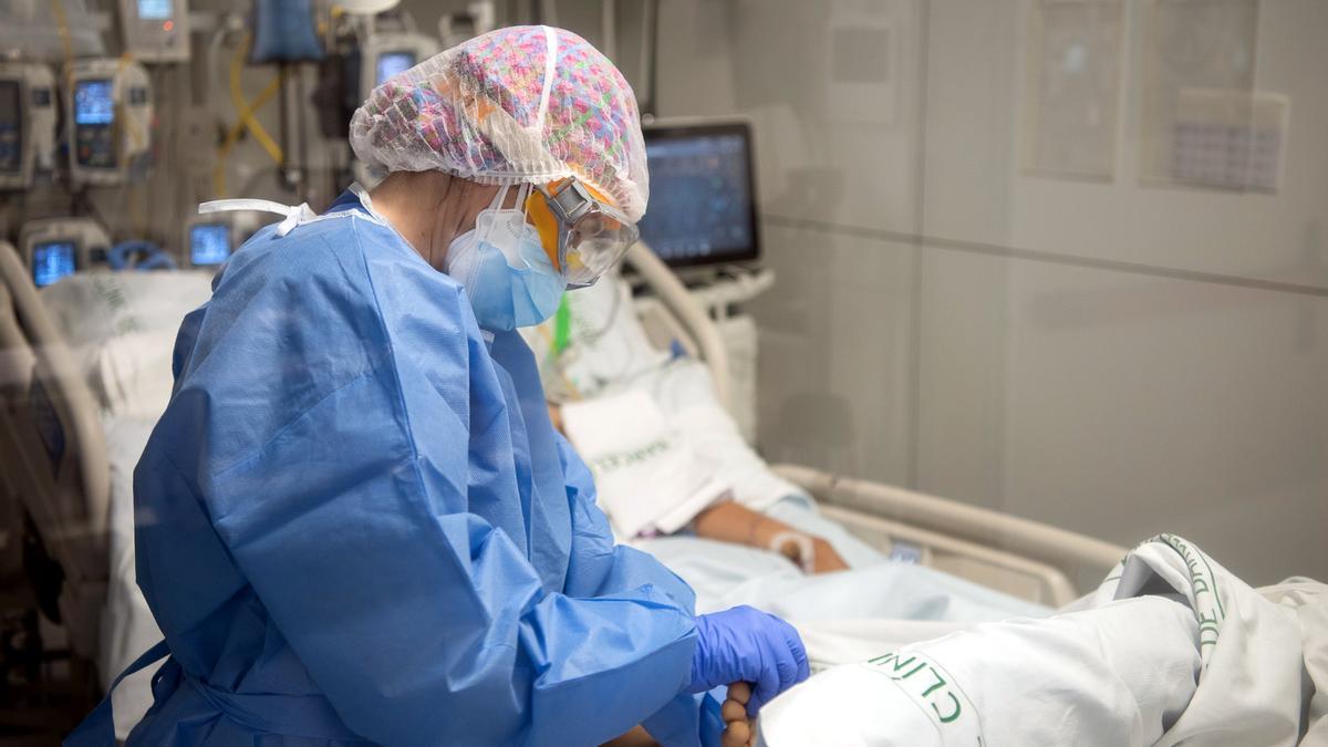 Una infermera fa un massatge al peu a un pacient ingressat a l'UCI, durant la cinquena onada de la pandèmia de la covid-19