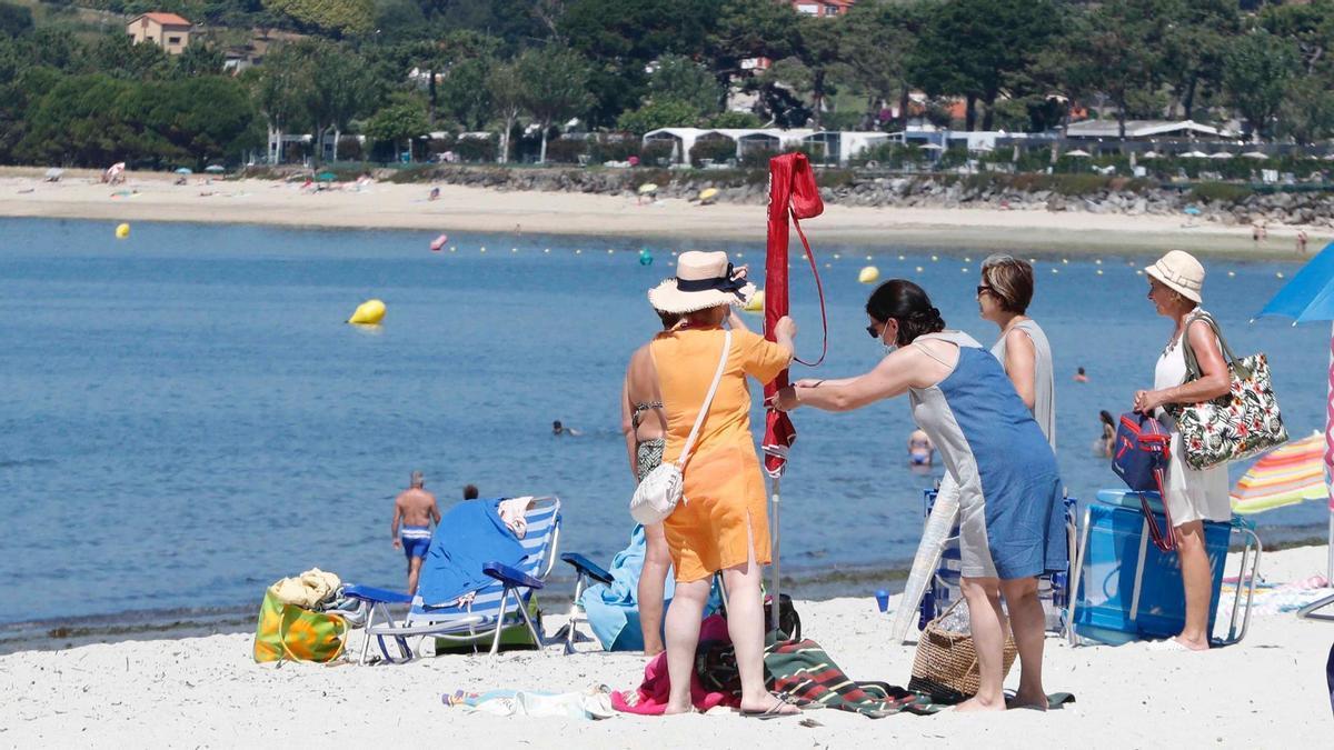Un grupo de mujeres planta una sombrilla en la playa de A Ladeira