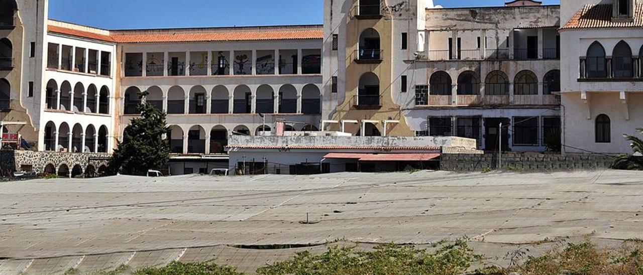 Edificio de los Salesianos de Guía con su templo y cultivos de plataneras de invernadero en su parte delantera.