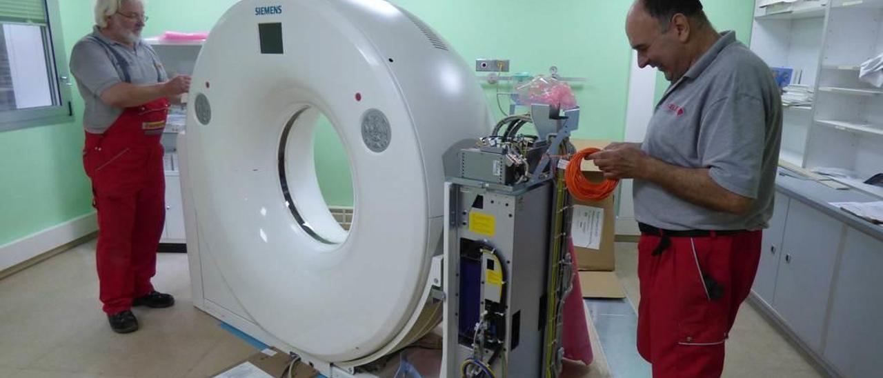Dos operarios instalan el TAC en el Hospital Comarcal de Cangas del Narcea.