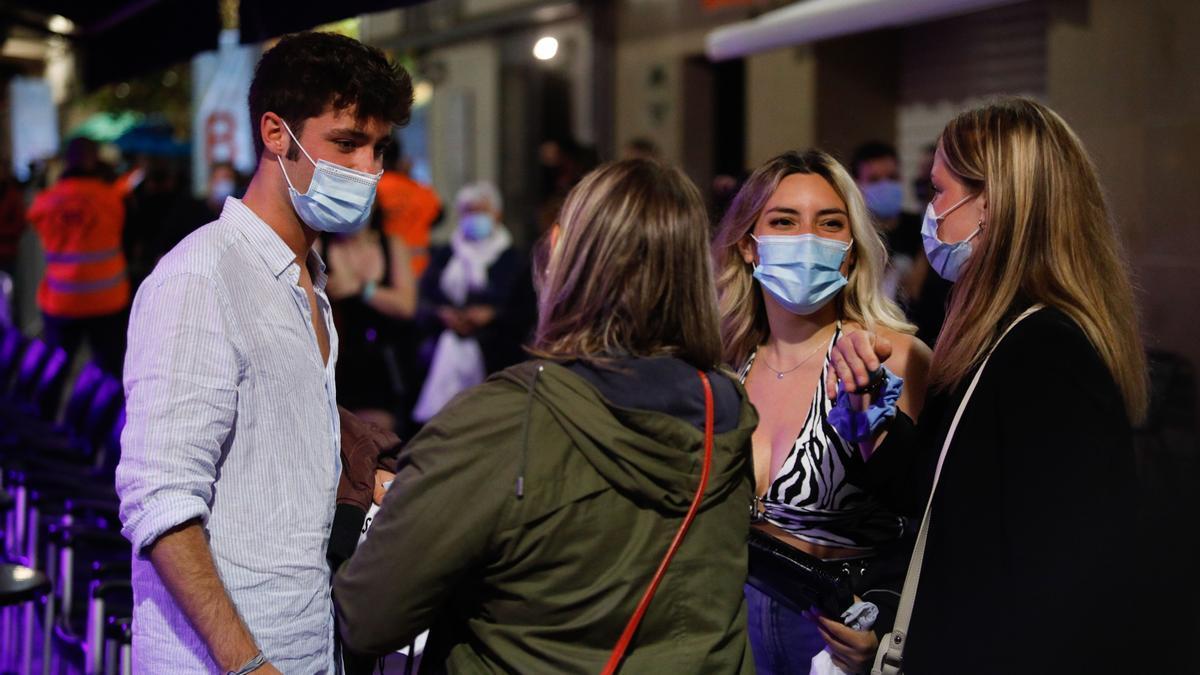 Algunas personas jóvenes en la calle con mascarilla.