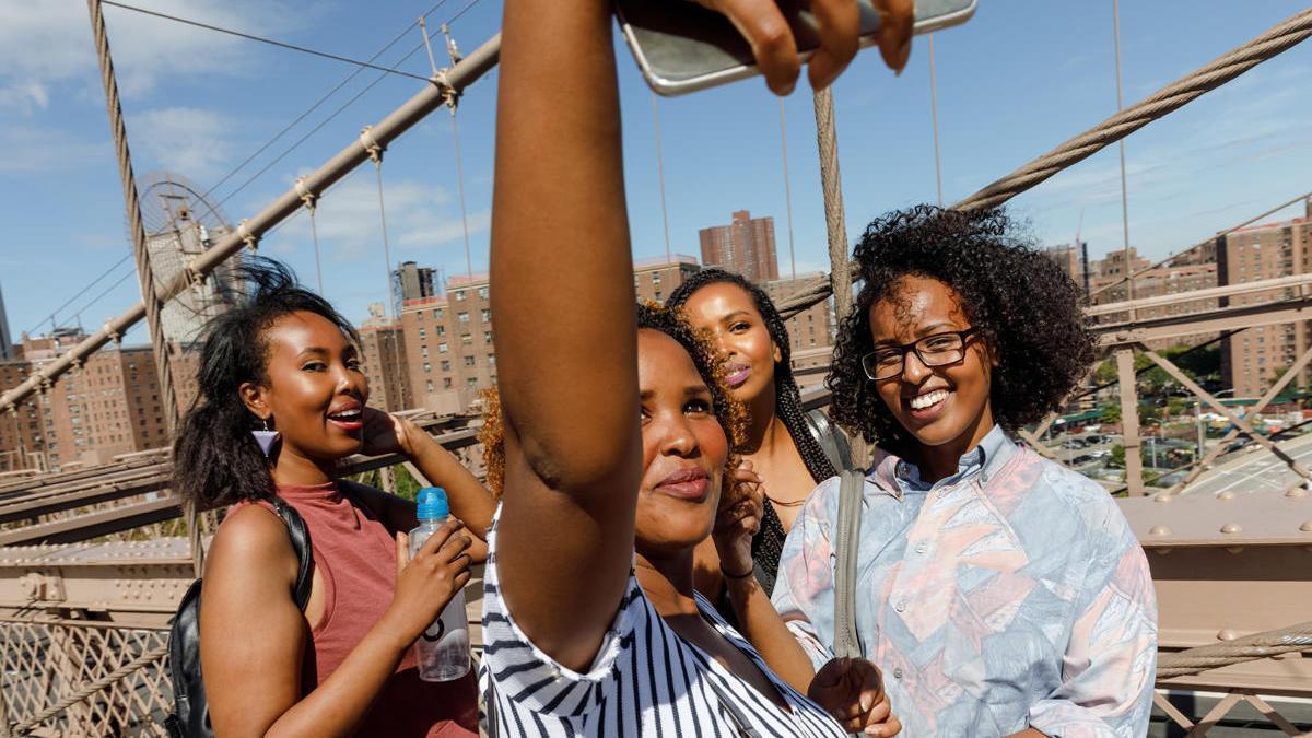 Varias personas se toman un 'selfie' con un teléfono móvil.