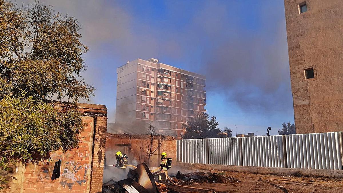 Los bomberos sofocan el fuego, con el muro de San Miguel de los Reyes a la derecha.  | LEVANTE-EMV