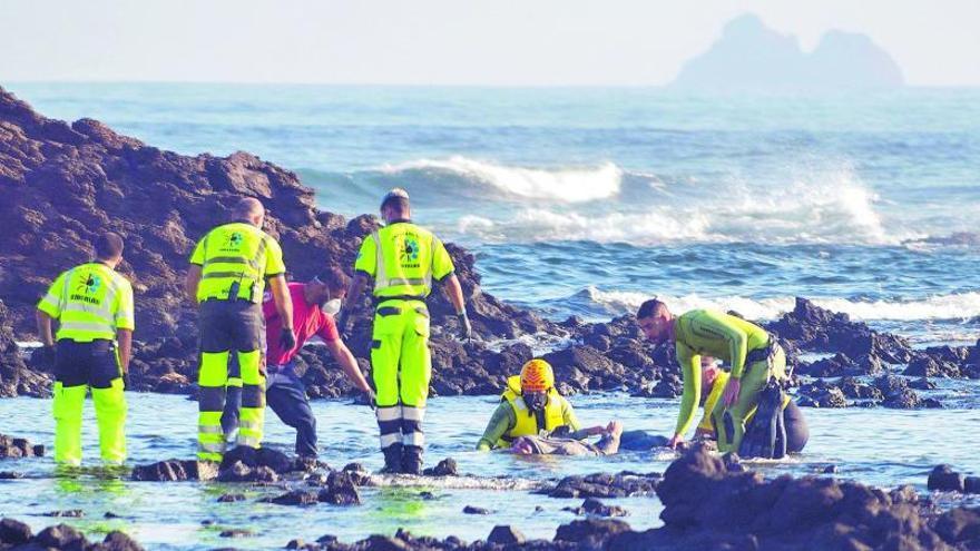 Efectivos de los servicios de emergencia rescatan un cadáver en la zona de Órzola en la que zozobró la patera la noche anterior.     JAVIER FUENTES (EFE)