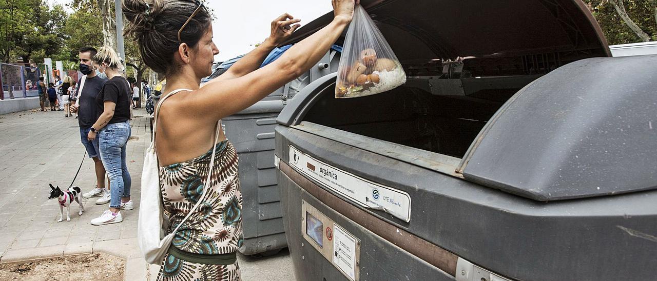 Una usuaria deposita basura en uno de los 88 contenedores de selectiva, de fracción orgánica, que existen ahora en Alicante.    PILAR CORTÉS