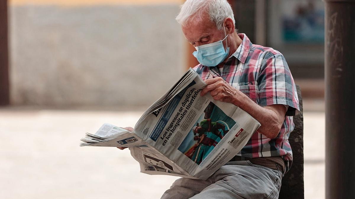 Un hombre lee el periódico en La Laguna durante estos días.