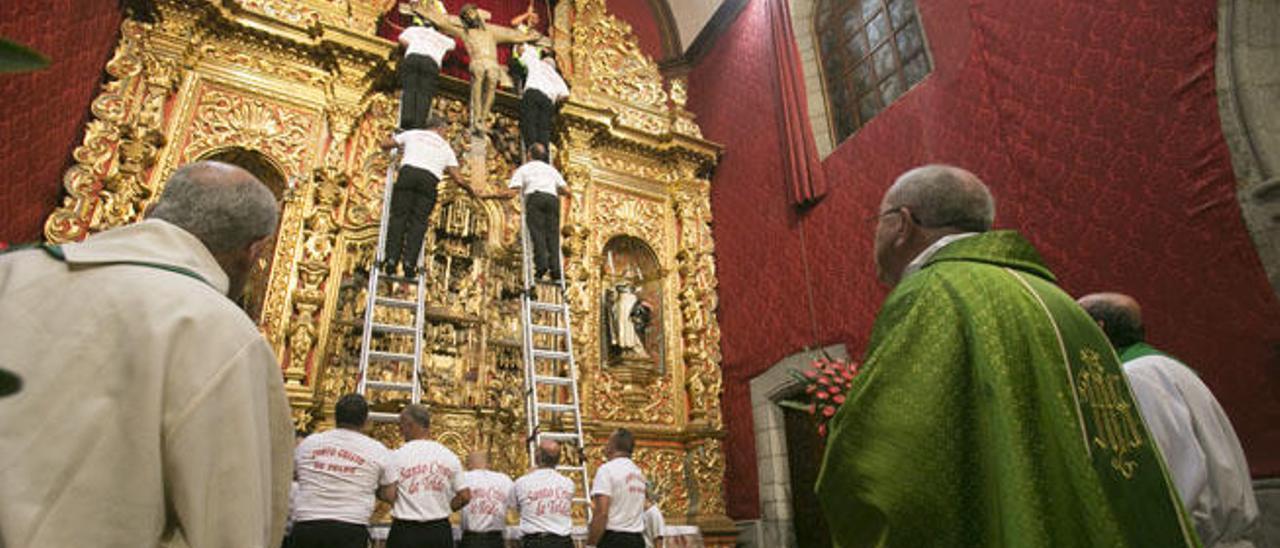 Los mayordomos bajan al Cristo de Telde desde la hornacina y el claretiano Vicente Cuadrado de verde.