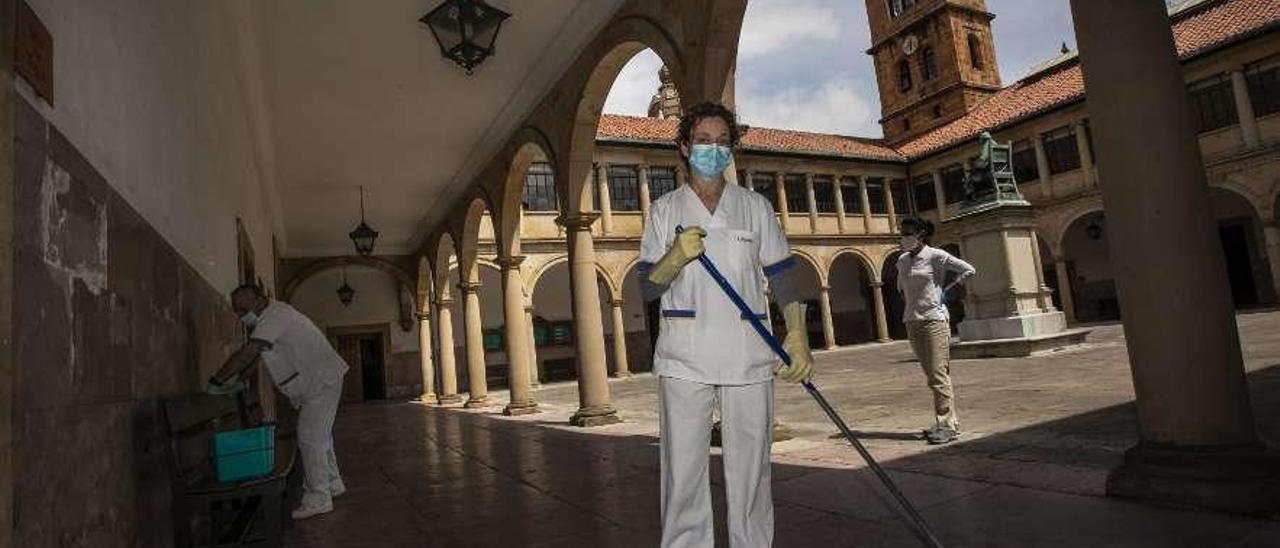 Susana Yagüe e Ismael Fernández, ayer, desinfectando el edificio histórico de la Universidad de Oviedo.