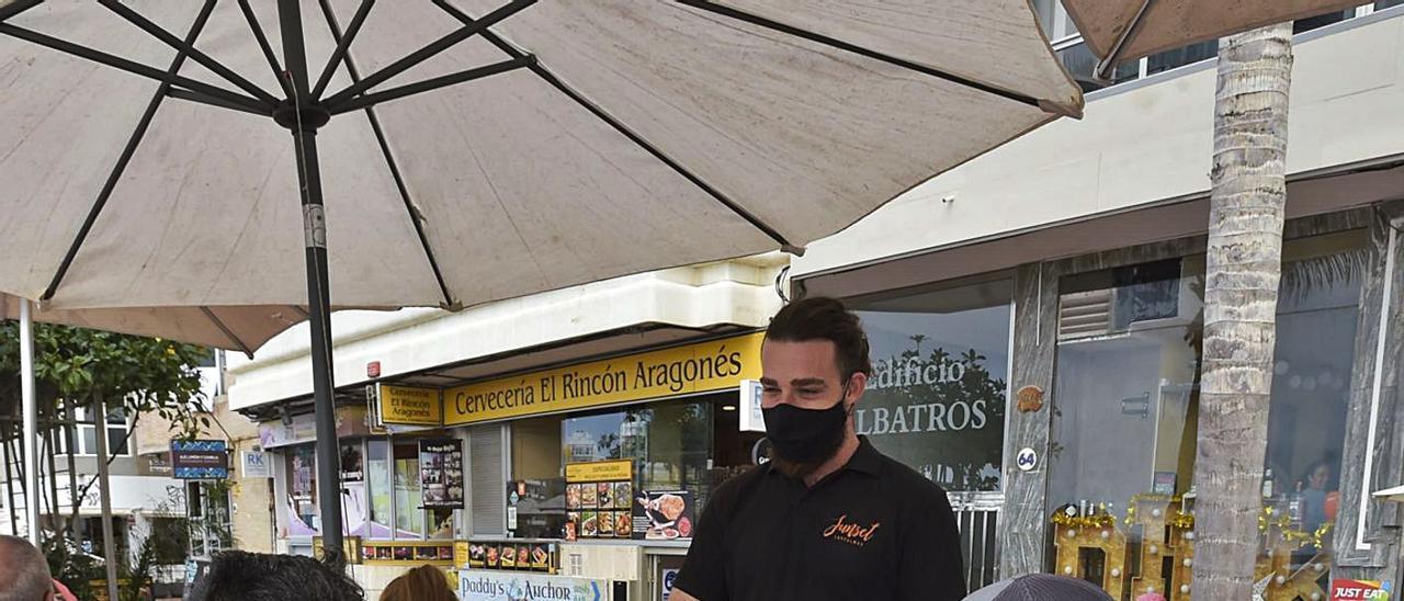 Un camarero atiende a unos clientes en una terraza de Las Canteras.     ANDRÉS CRUZ