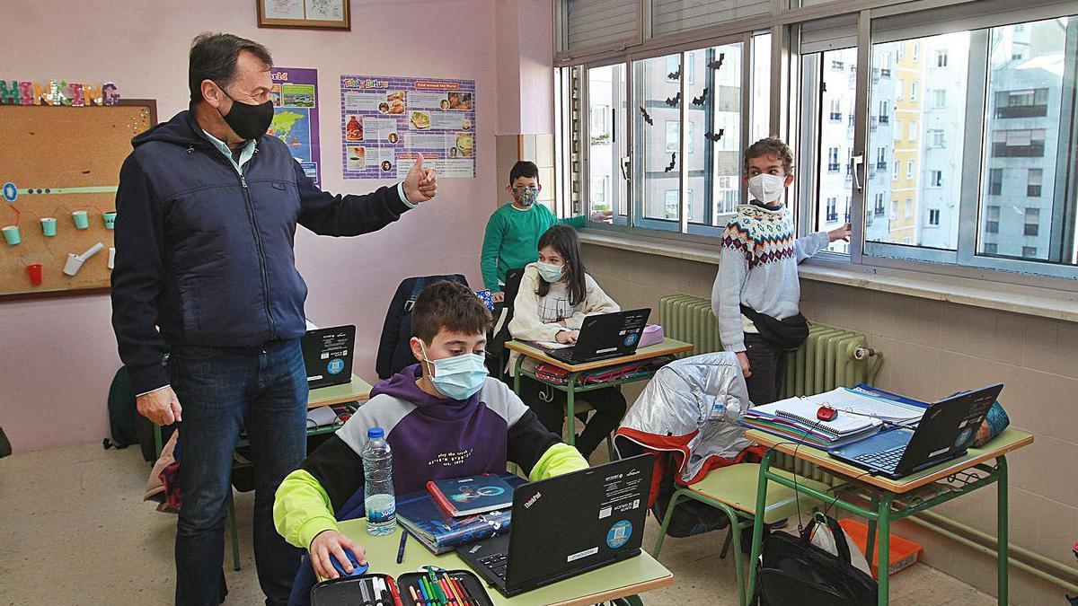 Dos alumnos abren las ventanas de su aula para ventilar, ante el director del Mestre Vide.   | // IÑAKI OSORIO
