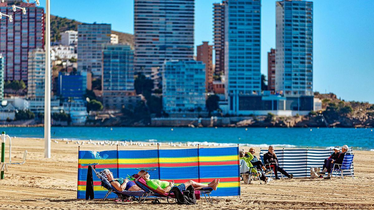 Turistas en una vacía playa de Levante de Benidorm el pasado jueves. En la misma semana de enero de 2020, la playa todavía estaba llena.  |
