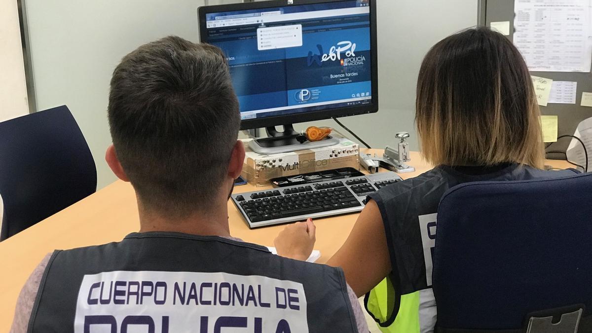 Agentes de la Policía Nacional delante de un ordenador.